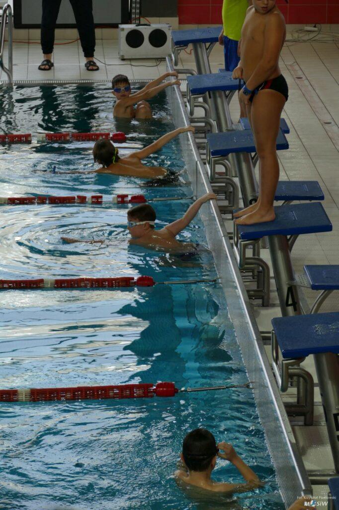 Młodzi zawodnicy na starcie zawodów pływackich.