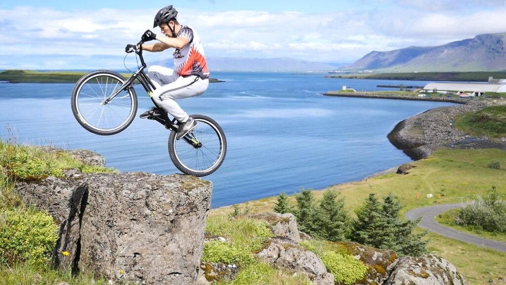 Akrobata rowerowy na skale. W tle zatoka