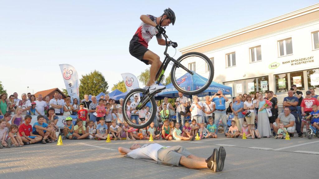 Akrobata przeskakujący na rowerze przez leżącego człowieka